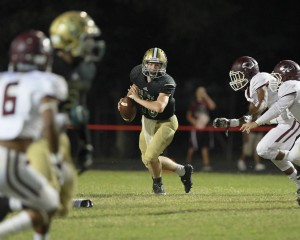 LC-M quarterback Beau Bickham looks downfield for an open receiver while evading two Silsbee defenders. (Mark Pachuca / The Orange Leader)