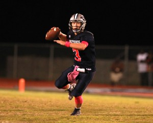 Mustangs quarterback Jack Dallas (3) rolls out for a pass against Newton on Friday night. (Mark Pachuca / The Orange Leader)